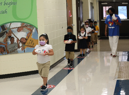 children walking in the hallway with social distancing